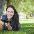 mixed race young female texting on cell phone outside — Stock Photo