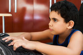 Cute hispanic boy typing on a computer — Stock Photo