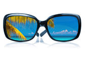 Sunglasses with a beach scene reflected on the glass — Stock Photo