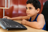 Hispanic child working with a computer — Stock Photo