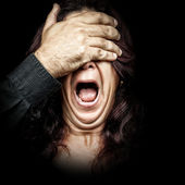 Woman screaming with a hand covering her eyes — Stock Photo