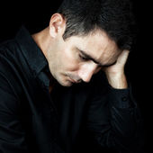 Worried and depressed man isolated on black — Foto Stock