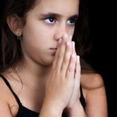 Hispanic girl praying isolated on black — Stock Photo