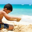 Hispanic boy building a sand castle — Stock Photo #11836781