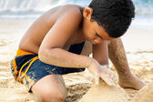 Hispanic boy building a sand castle — Stock Photo