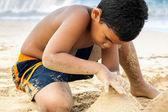 Rapaz latino-americano, um castelo de areia — Foto Stock
