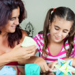Mother and daughter making origami - Stock Photo