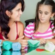 Mother and daughter making origami — Stock Photo #12116443