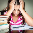 Angry and tired schoolgirl studying - Stock Photo