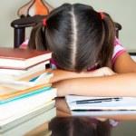 Exhausted girl sleeping on her desk — Stock Photo