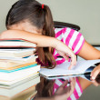 Tired schoolgirl sleeping on her desk — Stock Photo