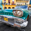Classic Cadillac in a colorful neighborhood in Havana — Stock Photo #12316197