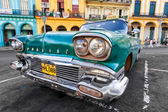 Classic Cadillac in a colorful neighborhood in Havana — Stock Photo