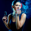 Charming spanish women with cigarette and gun — Stock Photo