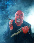 Angry red faced man with knife and cigar — Stock Photo