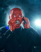 Dangerous man with red face talking to mobile phone. — Stock Photo
