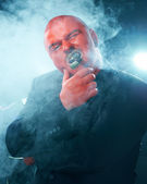 Mysterious man with red face smoking cigar. — Stock Photo