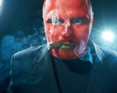 Angry man with red face smoking cigar. — Stock Photo