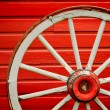 Wagon Wheel by Painted Red Wall - Stock Photo