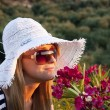 Young blond woman smelling flowers — Stockfoto
