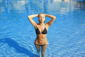 Young blond woman standing in swimming pool — Foto de Stock