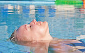 Young blond woman in swimming pool — Stock Photo