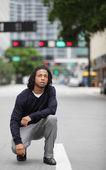 Hombre en cuclillas en la calle — Foto de Stock