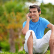 Young male with a mobile in park — Stock Photo