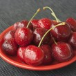 Cherries on a red plate — Stock Photo