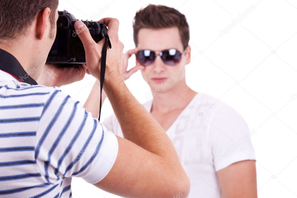 Young male fashion model posing for a professional photographer on white background. young man wearing sunglasses being photographed by a young artist  Stock Photo #10796973