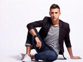 Junge mode mann sitzt entspannt — Stockfoto