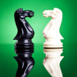 White and black knights facing aeach other — Stock Photo