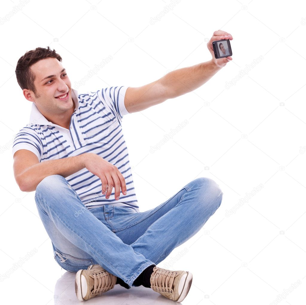 Young casual man taking a picture of him self using a smart phone — Stock Photo #11377812