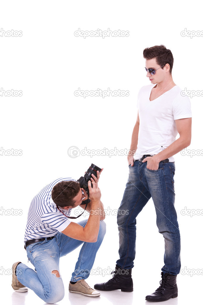 Young male fashion model posing for a professional photographer on white background. young man wearing sunglasses being photographed by a young artist — Stock Photo #11377820