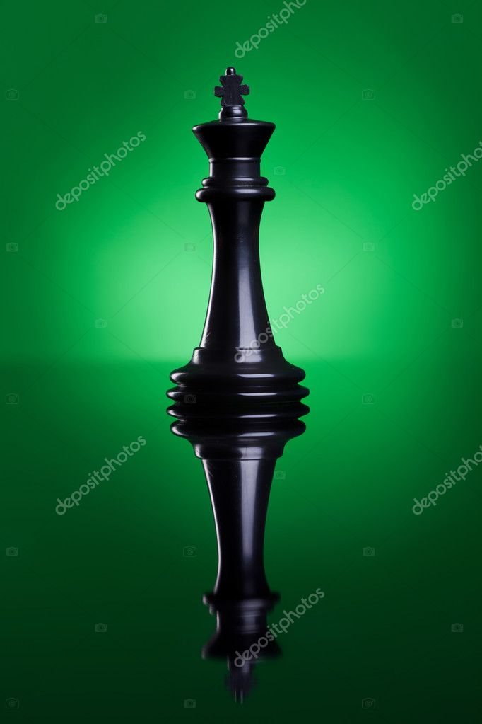 Piece of chess. The black king standing on a green background with a reflection — Stock Photo #11377878