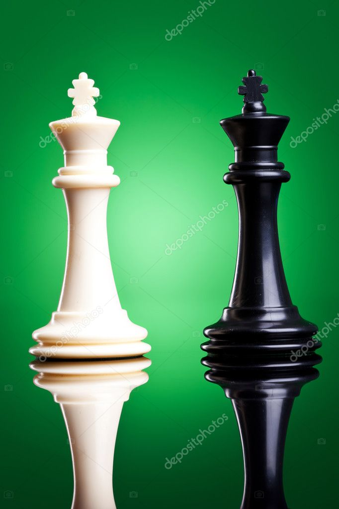 Black and white kings on green background with reflection - chess pieces  Stock Photo #11377896