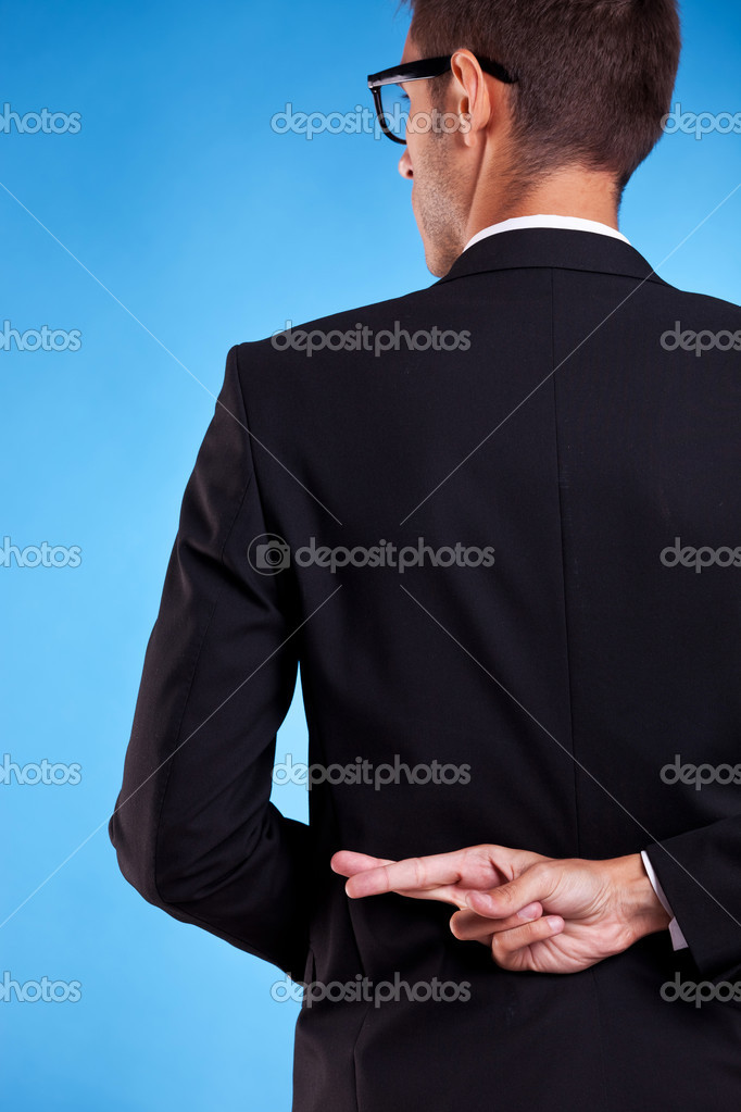 Business man with fingers crossed behind back isolated over white background  Stock Photo #11648944