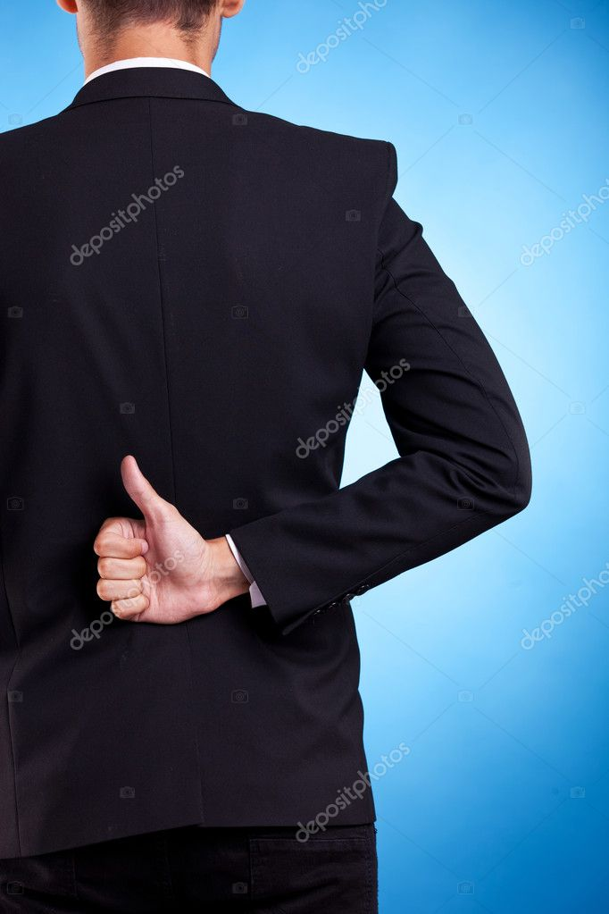 Business man hand with thumbs up ok sign at his back, on blue background — Stock Photo #11648980