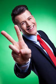 Business man in a suit giving the victory sign — Stock Photo