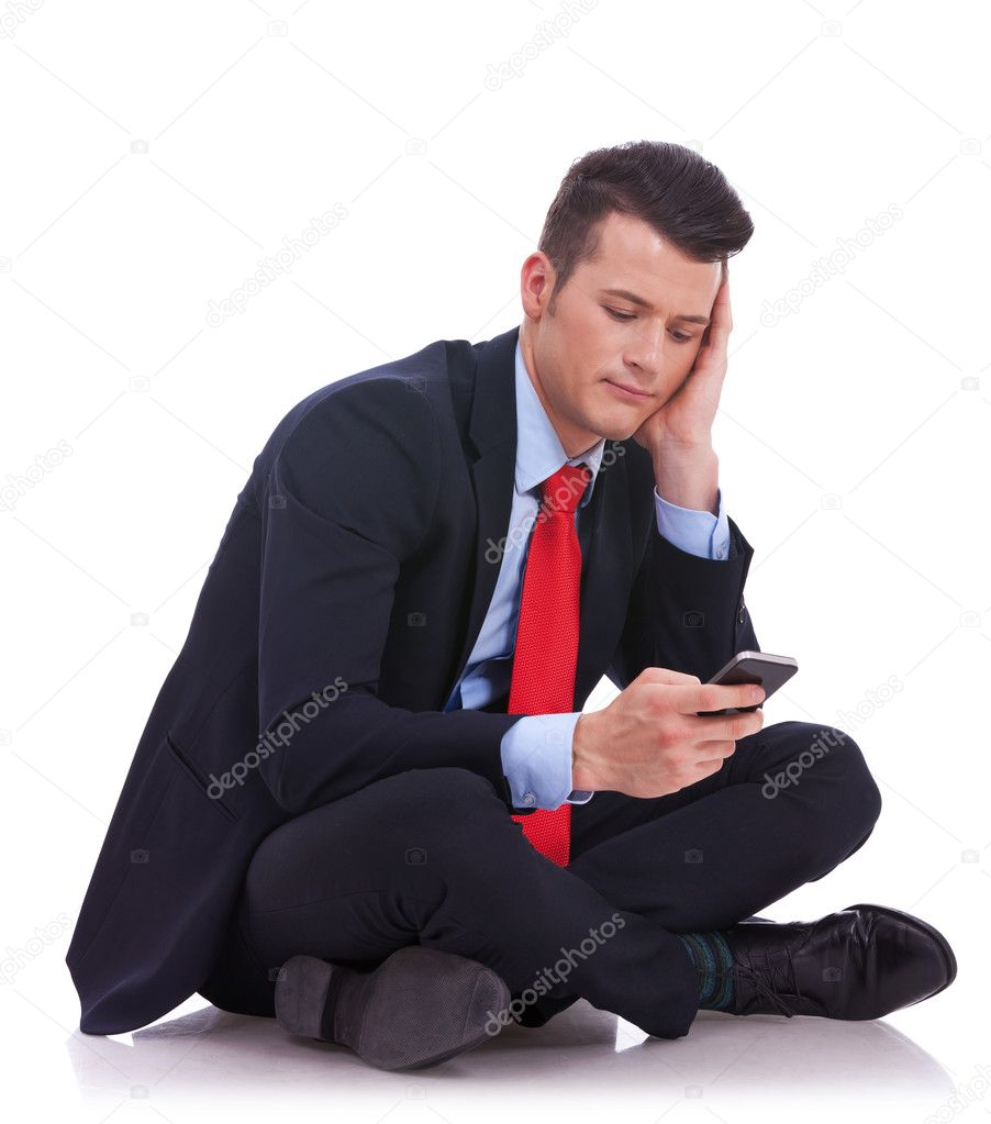 Pensive young business man is reading a text message while sitting on a white background  Stock Photo #11918860