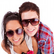 Young couple wearing sunglasses and smiling at you — Stock Photo #12396431