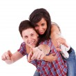 Young woman riding on her boyfriend's back and pointing — Stock Photo #12396436