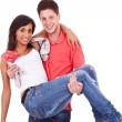 Young guy holding his girlfriend in his arms — Stock Photo