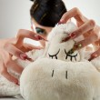 Young woman sticking her nails in her lamb toy — Stock Photo #12396524