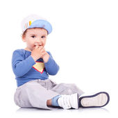 Lovely kid sitting and holding his hands in his mouth — Stock Photo