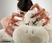 Jeune femme coller ses ongles dans son jouet d'agneau — Photo