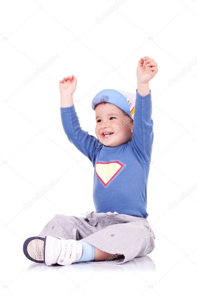 Happy boy sitting with arms raised and laughing while looking away from camera. Isolated on white — Stock Photo #12396458