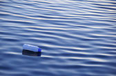 Plastic bottle floating on surface of water — Stock Photo
