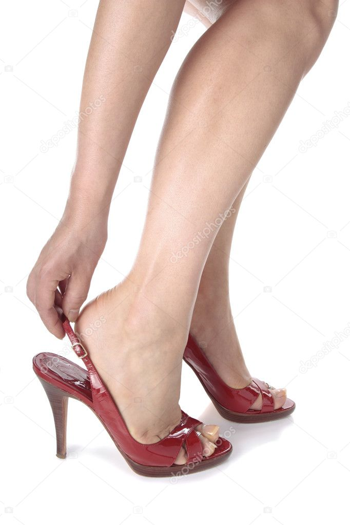 Woman putting on red heel shoes over white background — Stock Photo #10862735