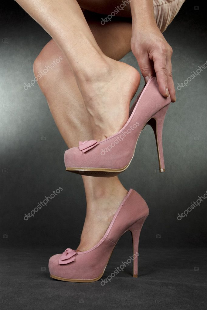 Woman putting on high heel shoes over grey background — Stockfoto #10864222